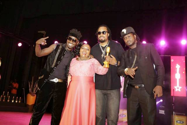 Joanita Kawalya poses with Navio, Bebe Cool and Bobi Wine after winning the lifetime achievement award