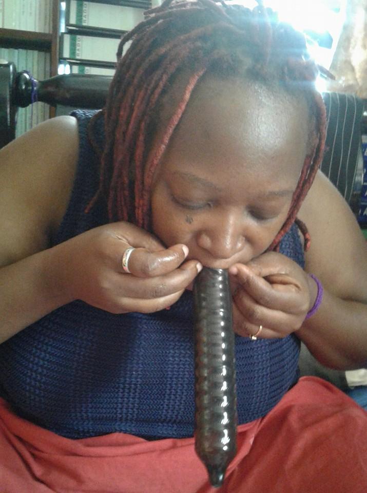 Dr Stella Nyanzi blowing air into a condom (FILE PHOTO)