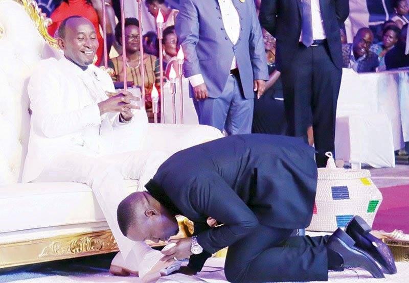 Joseph Kabuleeta kissing Mbonye's feet